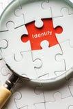 Chiuda sulla lente d'ingrandimento che cerca l'identità mancante di pace di puzzle fotografia stock