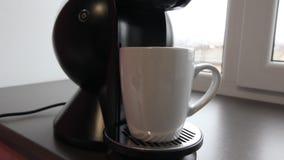 Chiuda sulla macchina della macchinetta del caffè con la tazza di caffè macchiato video d archivio