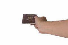 Chiuda sulla mano che giudica il passaporto della Tailandia isolato su backgr bianco fotografie stock libere da diritti