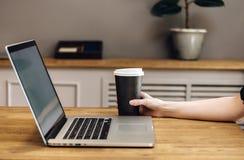 Chiuda sulla mano che tiene il caffè della tazza di carta di portano via bere fotografia stock libera da diritti
