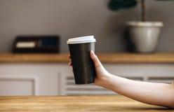 Chiuda sulla mano che tiene il caffè della tazza di carta di portano via bere immagine stock libera da diritti