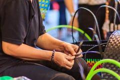 Chiuda sulla mano del tessitore durante il canestro di tessitura fatto da plastica Fotografia Stock Libera da Diritti