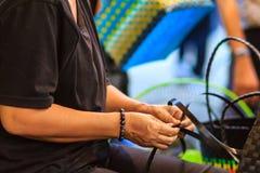 Chiuda sulla mano del tessitore durante il canestro di tessitura fatto da plastica Immagine Stock Libera da Diritti