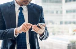 Chiuda sulla mano dell'uomo d'affari facendo uso del telefono cellulare vicino al vento dell'ufficio immagine stock libera da diritti