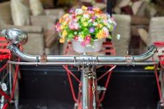 Chiuda sulla mano della bicicletta e sul fuoco selettivo dei fiori attuali Fotografia Stock