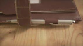 Chiuda sulla mano della donna del colpo che mette il pennino d'acciaio d'argento in tavola quotidiana di legno del supporto del t stock footage