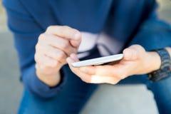 Chiuda sulla mano della donna facendo uso del telefono cellulare fuori con luce solare, sel Fotografia Stock