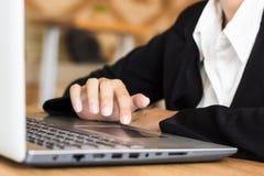 Chiuda sulla mano di uso della donna di affari un computer portatile lavorare in una caffetteria o in un ufficio Fotografie Stock Libere da Diritti