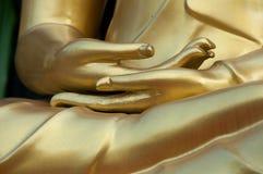 Chiuda sulla mano dorata nell'azione di meditazione Fotografie Stock