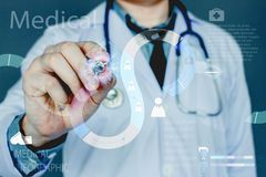 Chiuda sulla mano Medico tiene con il punto di penna con il infographics digitale medico di dati su fondo blu fotografia stock