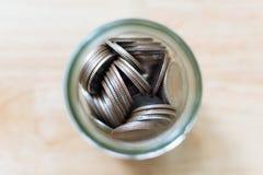 Chiuda sulla moneta di vista superiore in vetro da bottiglia del barattolo sulla tavola, risparmi i soldi Immagini Stock