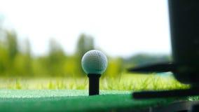Chiuda sulla palla sul giocatore di golf pensionato T che prende l'oscillazione che colpisce la palla da golf fuori dal T sul cam Fotografia Stock Libera da Diritti