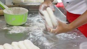 chiuda sulla pasta d'impastamento del cuoco unico delle mani per pizza stock footage