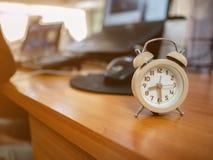 Chiuda sulla piccola sveglia sullo scrittorio funzionante nell'ufficio immagini stock