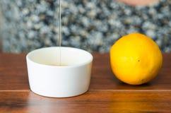 Chiuda sulla piccola tazza bianca che si siede sullo scrittorio di legno con miele che cade in da sopra, limone dal lato Immagine Stock Libera da Diritti
