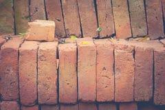 Chiuda sulla pila di mattoni marroni con sfondo naturale verde al cantiere Fotografie Stock