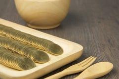 Chiuda sulla pila di monete di oro in vassoio di legno Fotografie Stock