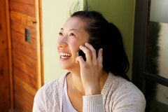 Chiuda sulla seduta asiatica sorridente della donna esterna e sulla fabbricazione della telefonata Fotografia Stock Libera da Diritti