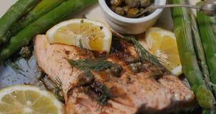 Chiuda sulla spinta in considerazione di un salmone organico arrostito delizioso con i capperi e l'aneto video d archivio