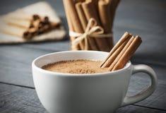 Chiuda sulla tazza bianca della bevanda calda lattea del salep della Turchia con la spezia sana della polvere della cannella Fotografia Stock