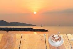 Chiuda sulla tazza di caffè macchiato sulla tavola di legno e sulla vista del fondo dell'alba o del tramonto fotografia stock
