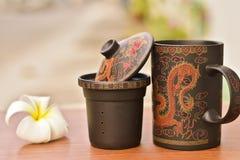 Chiuda sulla tazza di tè tradizionale e sul fiore bianco Immagini Stock