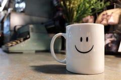 Chiuda sulla tazza felice sorridente della tazza di caffè sulla tavola del metallo fotografie stock