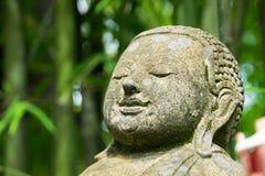 Chiuda sulla testa Buddha scolpito dalla pietra in parco di bambù fotografia stock