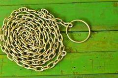 Chiuda sulla vecchia catena del metallo su di legno verde Immagini Stock Libere da Diritti