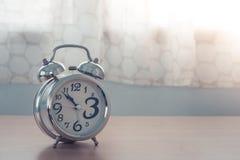 Chiuda sulla vecchia sveglia d'argento sulla tavola di legno in camera da letto con la tenda bianca nei precedenti fotografia stock