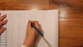 Chiuda sulla vista al disegno della mano del bambino su carta Il disegno della scala con si corregge stock footage
