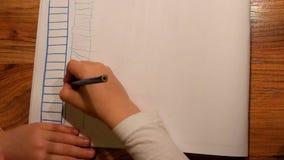 Chiuda sulla vista al disegno della mano del bambino su carta Il disegno della scala con si corregge video d archivio