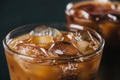 chiuda sulla vista dei cubetti di ghiaccio in caffè preparato il freddo in vetro su fondo scuro fotografie stock libere da diritti