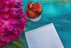 Chiuda sulla vista del blocco note e della tazza di fragole immagini stock