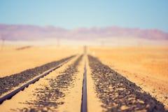 Chiuda sulla vista del dettaglio delle piste del treno che conducono attraverso il deserto vicino alla città di Luderitz in Namib Fotografia Stock