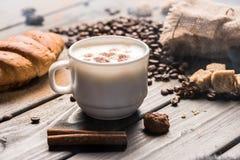 Chiuda sulla vista della tazza di caffè con i bastoni ed i biscotti di cannella Fotografia Stock