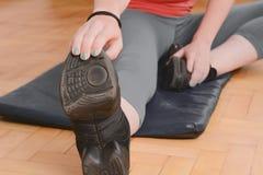 Chiuda sulla vista delle gambe streching della donna di sport Immagini Stock Libere da Diritti