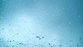 Chiuda sulla vista delle gocce di acqua che cadono sul vetro Pioggia che corre giù sulla finestra Stagione delle pioggie, autunno archivi video
