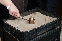Chiuda sulla vista di caffè turco pronta sulla sabbia dorata calda Concetto della preparazione del caffè Fotografie Stock Libere da Diritti