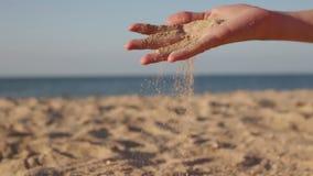 Chiuda sulla vista di sabbia di mare che passa le mani di una donna contro un oceano vago concettuale delle vacanze estive video d archivio