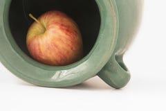 Chiuda sulla vista di una mela rossa dentro il barattolo di terra verdastro Immagini Stock