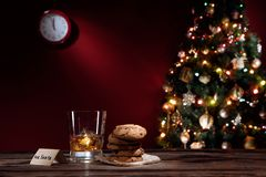 Chiuda sulla vista di vetro di whiskey con i biscotti sulla parte posteriore di colore Immagini Stock Libere da Diritti