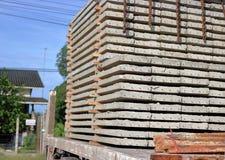 Chiuda sulla vista laterale del camion mentre pila del carico di lastre del calcestruzzo precompresso per costruzione immagine stock