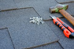 Chiuda sulla vista sulle assicelle del bitume dell'asfalto su un tetto con il martello, i chiodi ed il fondo del coltello della c Immagine Stock Libera da Diritti