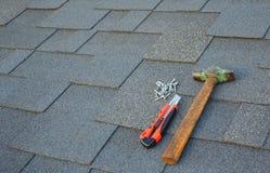 Chiuda sulla vista sulle assicelle del bitume dell'asfalto su un tetto con il martello, i chiodi ed il fondo del coltello della c Immagini Stock Libere da Diritti