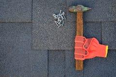 Chiuda sulla vista sulle assicelle del bitume su un tetto con il martello, i chiodi ed il fondo del coltello della cancelleria Fotografie Stock