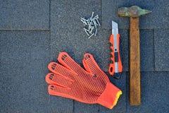 Chiuda sulla vista sulle assicelle dell'asfalto del bitume su un tetto con il martello, i chiodi ed il coltello della cancelleria Fotografie Stock