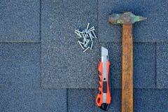 Chiuda sulla vista sulle assicelle dell'asfalto su un tetto con il martello, i chiodi ed il coltello della cancelleria Immagine Stock Libera da Diritti