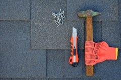 Chiuda sulla vista sulle assicelle dell'asfalto su un tetto con il martello, i chiodi ed il coltello Uso dei guanti nella costruz Fotografia Stock Libera da Diritti