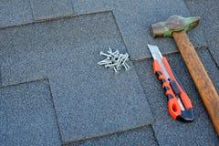 Chiuda sulla vista sulle assicelle dell'asfalto su un tetto con il martello, i chiodi ed il fondo del coltello Immagini Stock Libere da Diritti